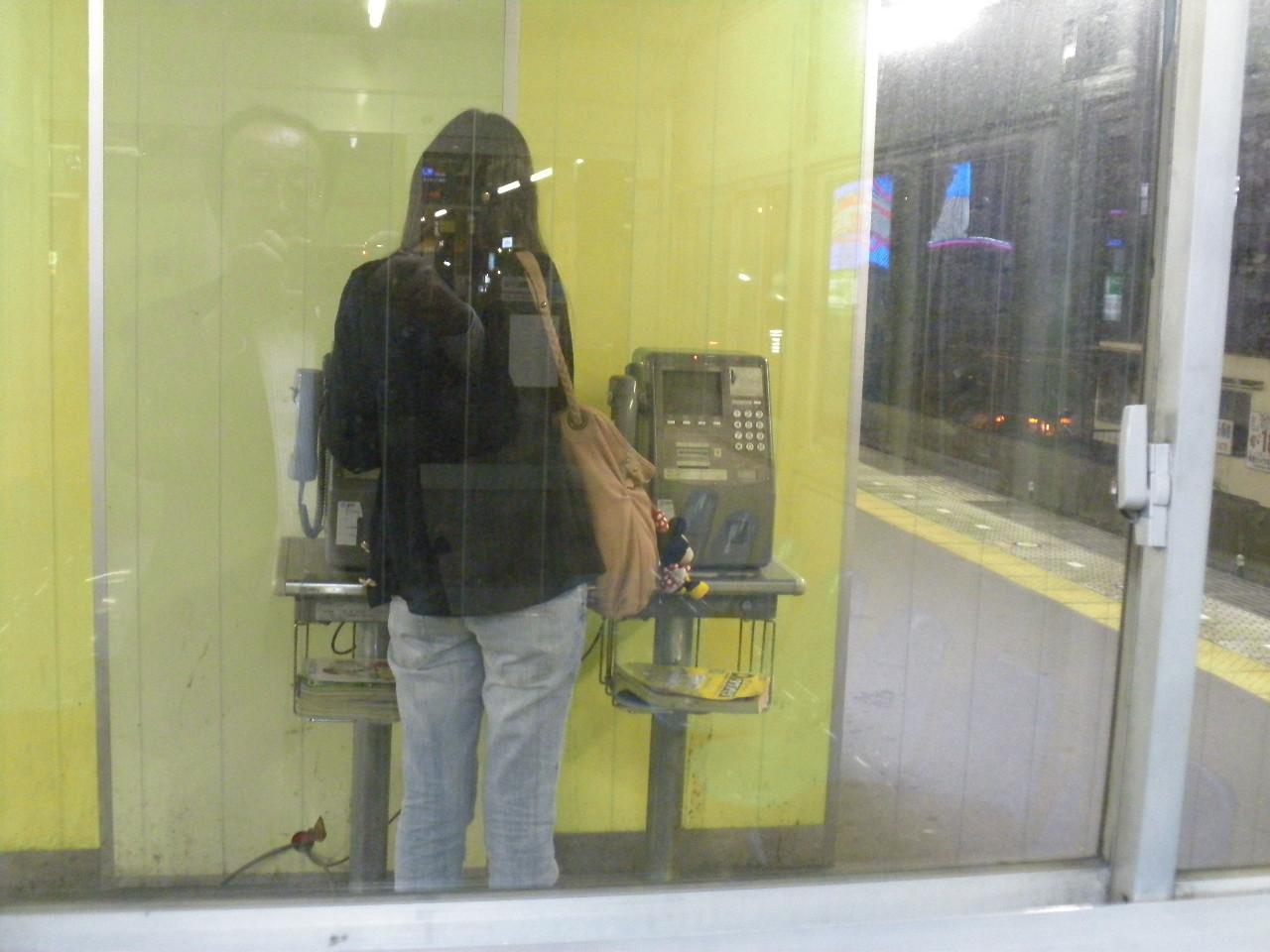 駅で見かけた公衆電話をかける若い女性